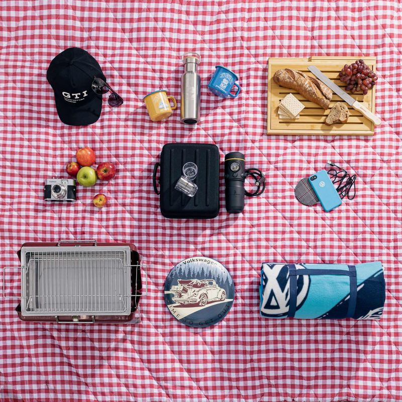 Volkswagen lifestyle products on a picnic blanket – from grill to GTI cap