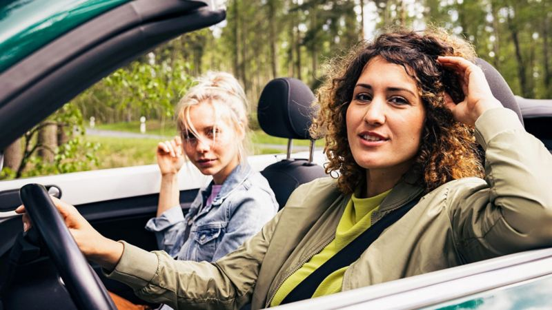 Two woman sitting in the front seats of VW car