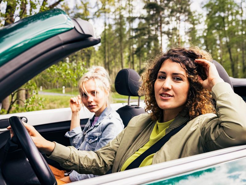 Two young women on the road in their Beetle Cabriolet – outdoor trip