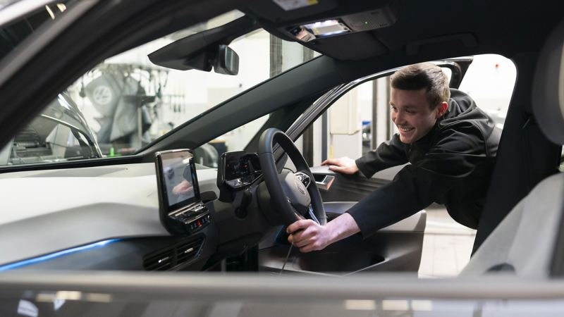A VW mechanic inspecting the inside cockpit of a VW ID.3