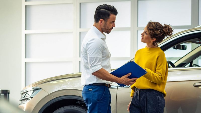 A customer talking to a VW employee in a showroom