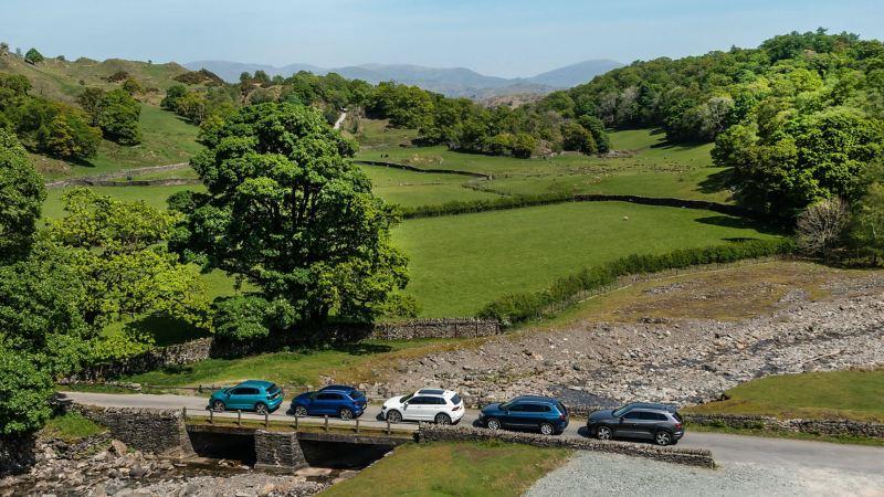 A range of VW SUVs driving accross a bridge