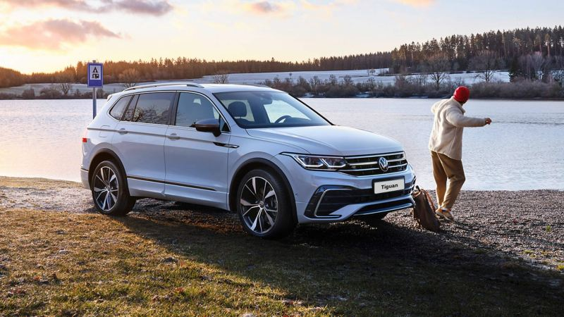 A white Tiguan Allspace R-Line with tinted rear windows and switched-on light signature stands on the lakeshore.