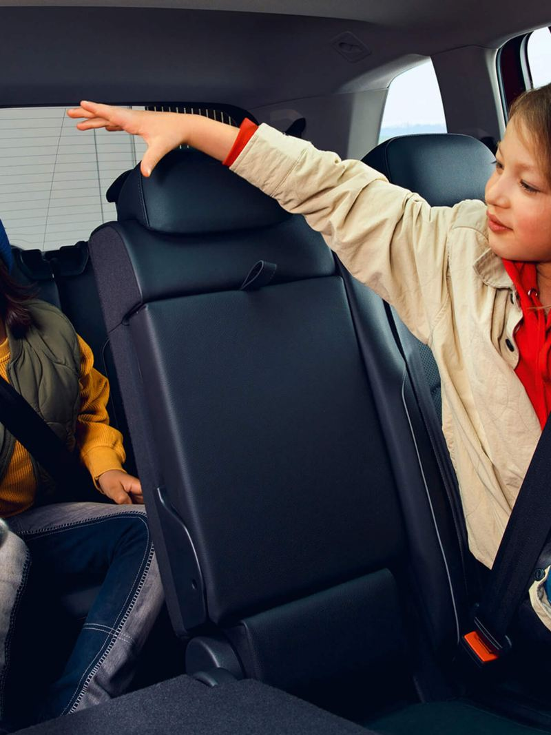 Two children sit in the interior of a Tiguan Allspace Elegance: a girl in the second row of seats, a boy in the third row.