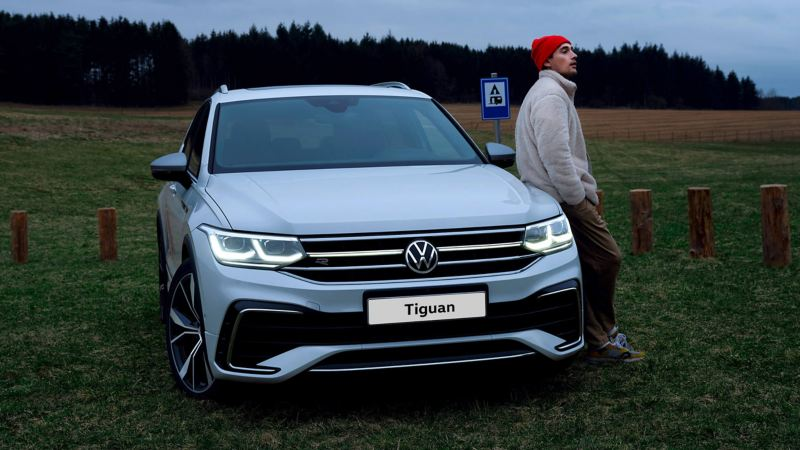 A man leans against the hood of a white Tiguan Allspace R-Line, the LED matrix headlights and light bar on.