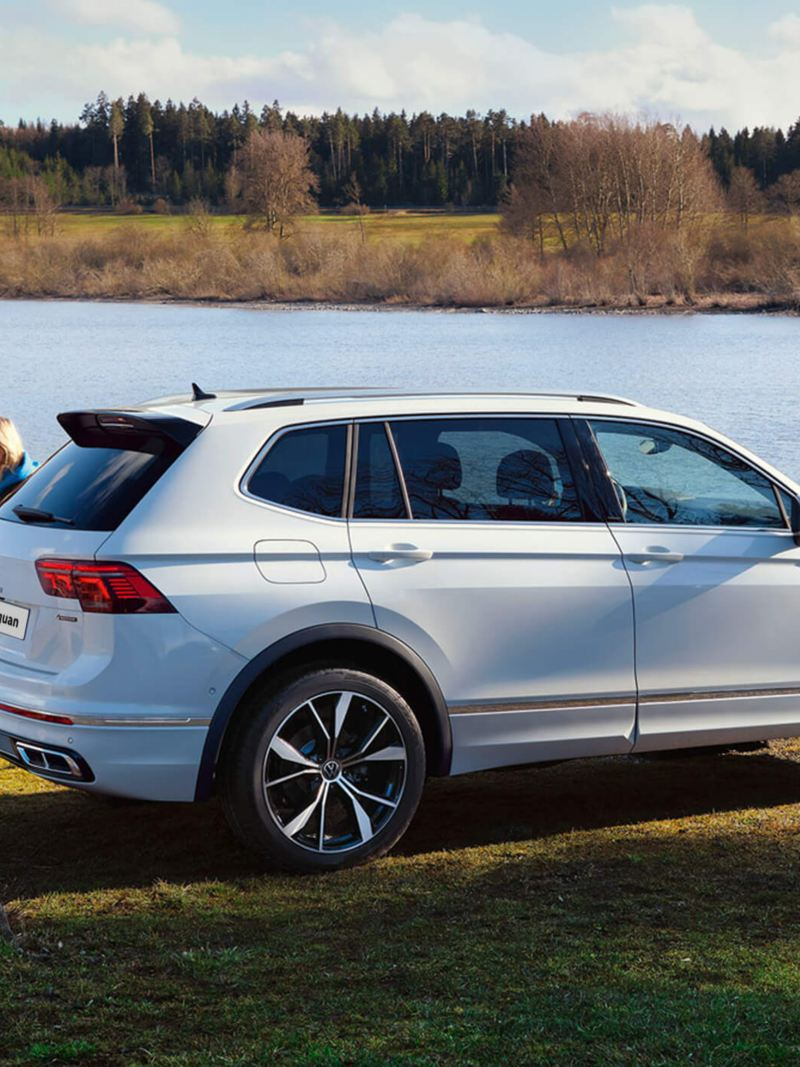 A group of young people walk past a white Tiguan Allspace R-Line parked by a lake.
