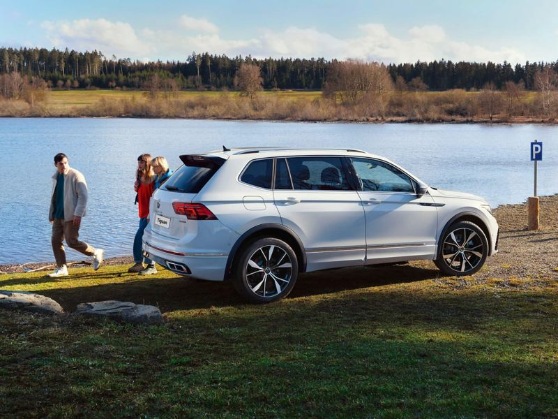 A white VW Tiguan parked by a lake with a family walking beside it