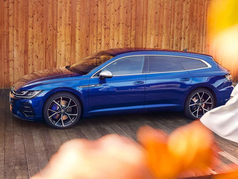 The new Arteon R Shooting Brake parked in front of a wooden fence