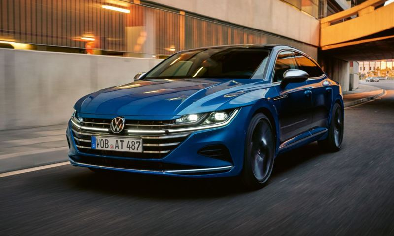 A view of the front of a blue New Arteon driving on the road.