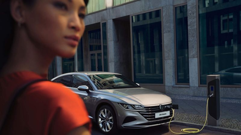 A woman charging her Arteon at the side of the road