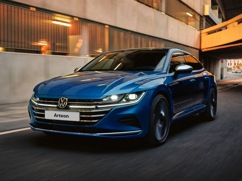 A blue VW Arteon plug in hybrid driving down a motorway with headlights on