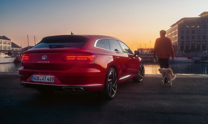 A man and his dog walking passed the new Arteon Shooting Brake