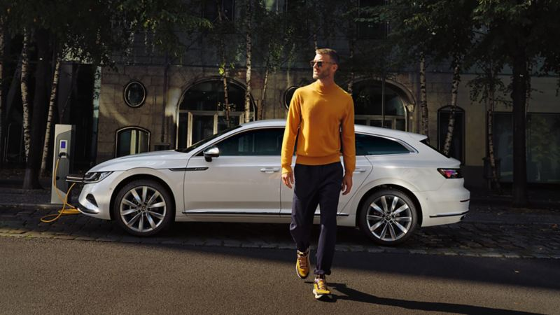 A man charging his Arteon Shooting Brake at the side of the road