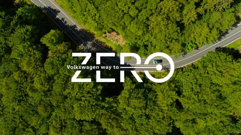Way to zero logo with an areal shot of a road running through woodland