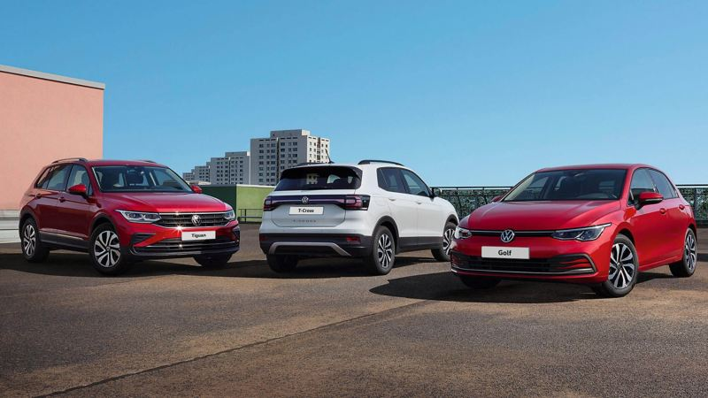 VW ACTIVE special edition models. Range with red Golf ACTIVE, white T-Cross ACTIVE and red Tiguan ACTIVE. Urban setting.