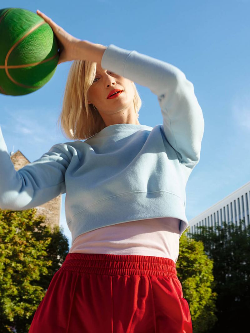 Woman playing basketball with green basketball in both hands