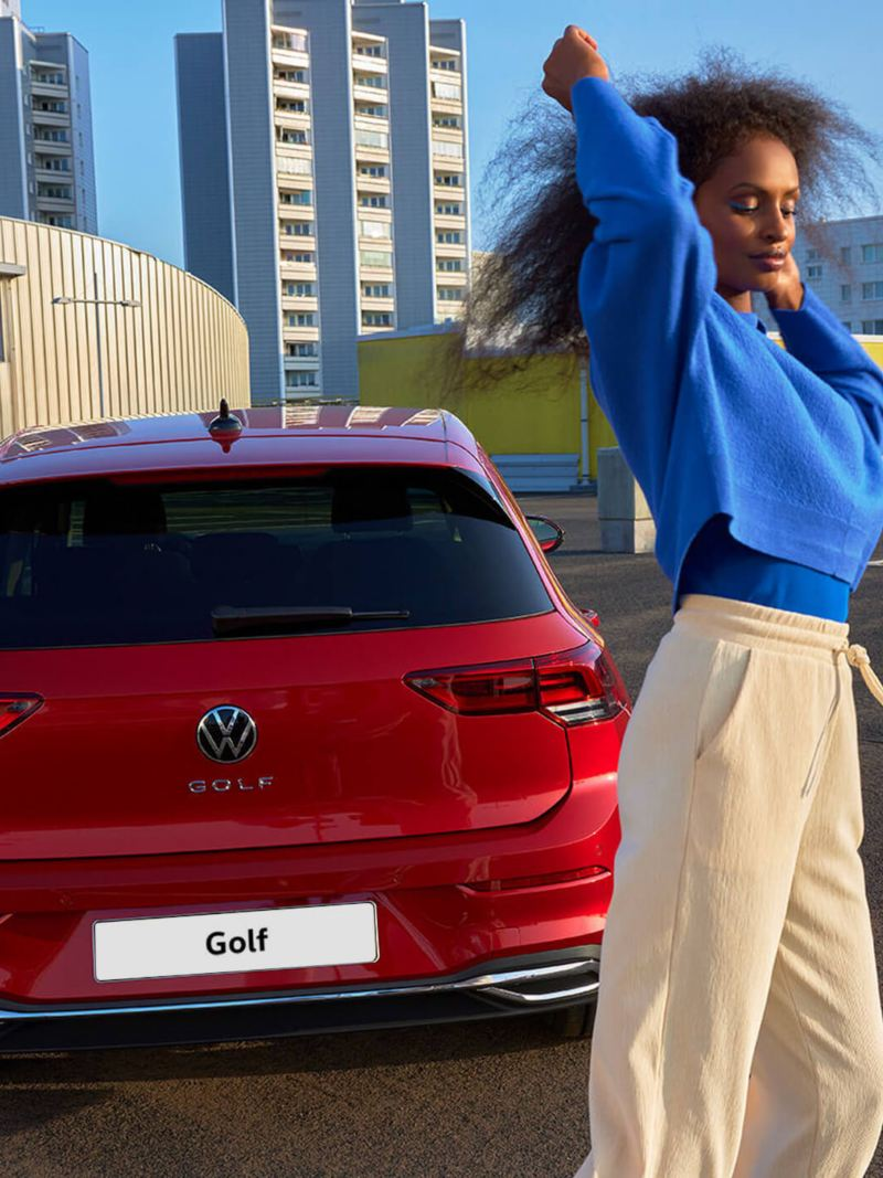Rear view of the red VW Golf ACTIVE. A woman stands in front of it.