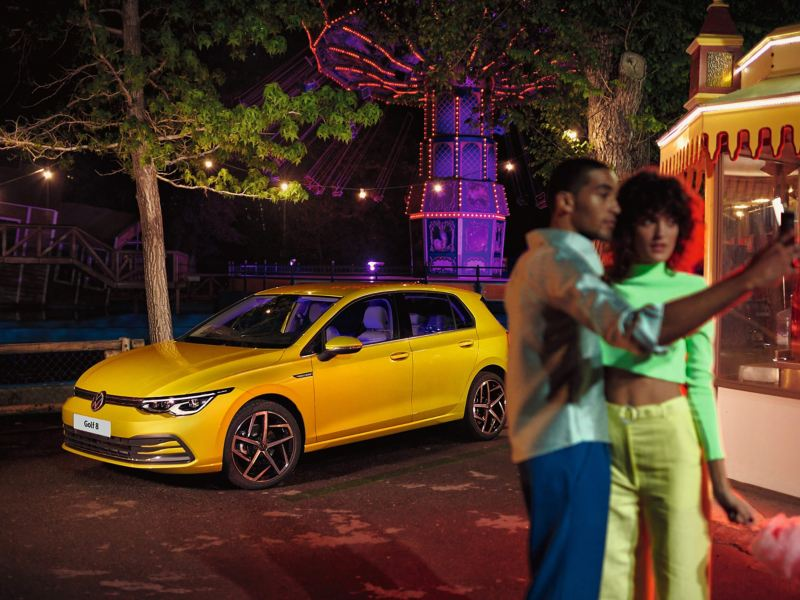 A couple talking at a fair with a yellow Golf 8 in the background.
