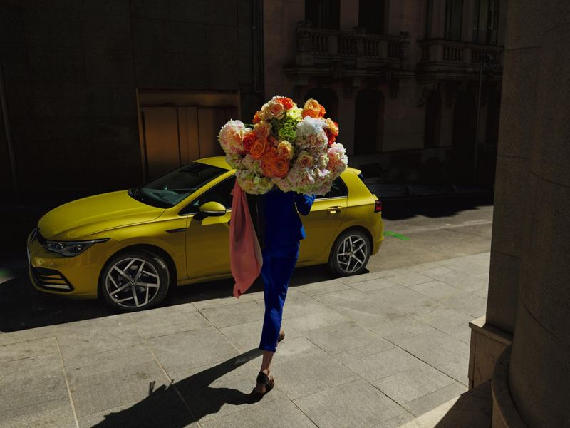 A woman walking with a bunch of flowers past a yellow Golf 8.