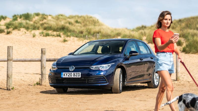 A blue new Golf 8 at the beach and a lady walking past with her dog