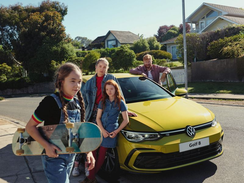 A girl carrying a skateboard walking past a yellow Golf 8, with a family standing around it.