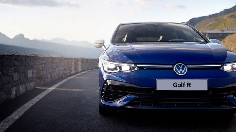 The new Golf R on a mountain road, seen from the front. Mountains are in the background.