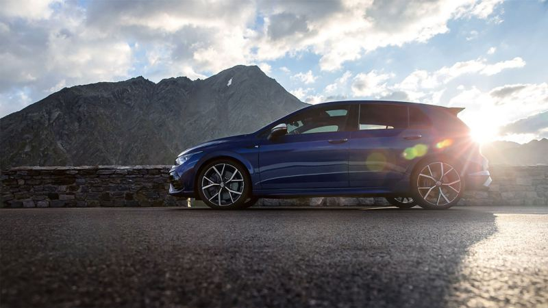 The new Golf R stands on a mountain road. In the background mountains, clouds and sun.