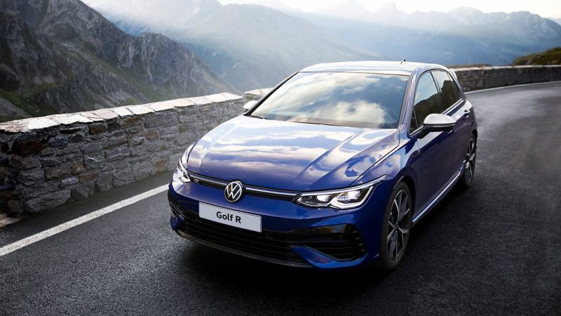 The new Golf R drives on the edge of a mountain road. Mountains are in the background.