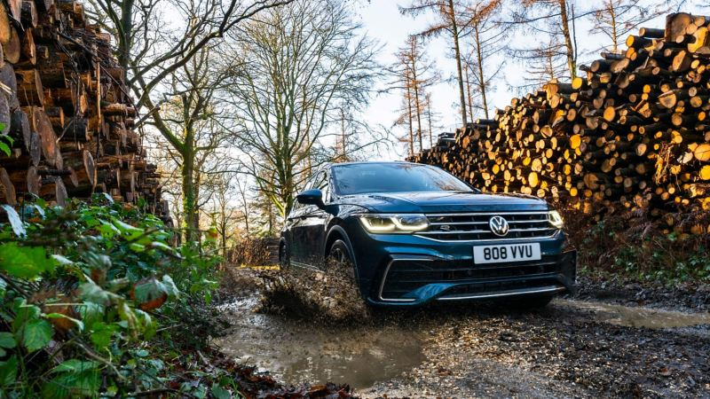 A blue Volkswagen Tiguan drives through a deep puddle on a gravel road