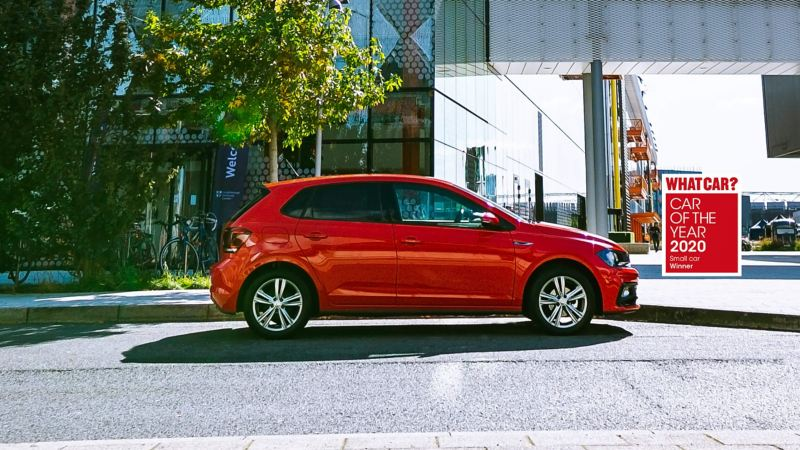 A red Volkswagen Polo parked outside an office building.