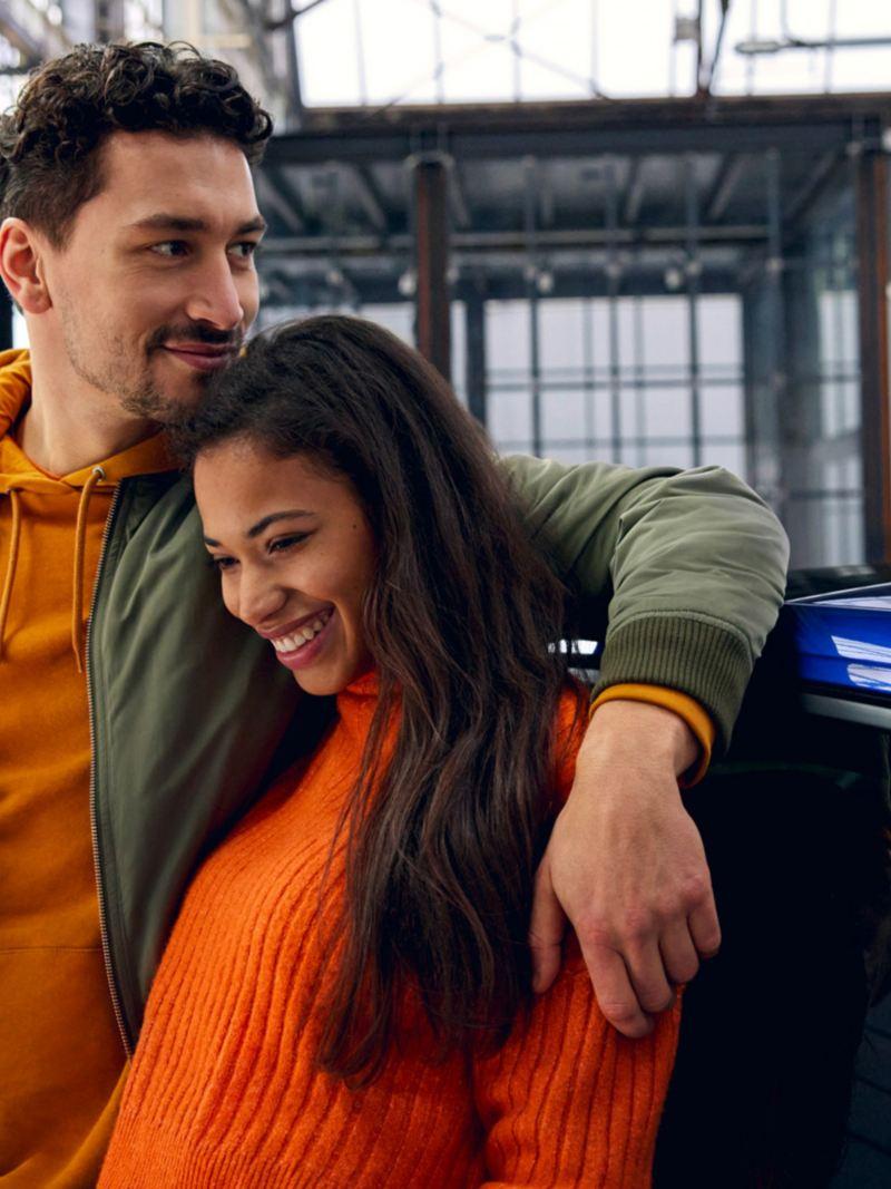 A couple leans against a new blue Polo.