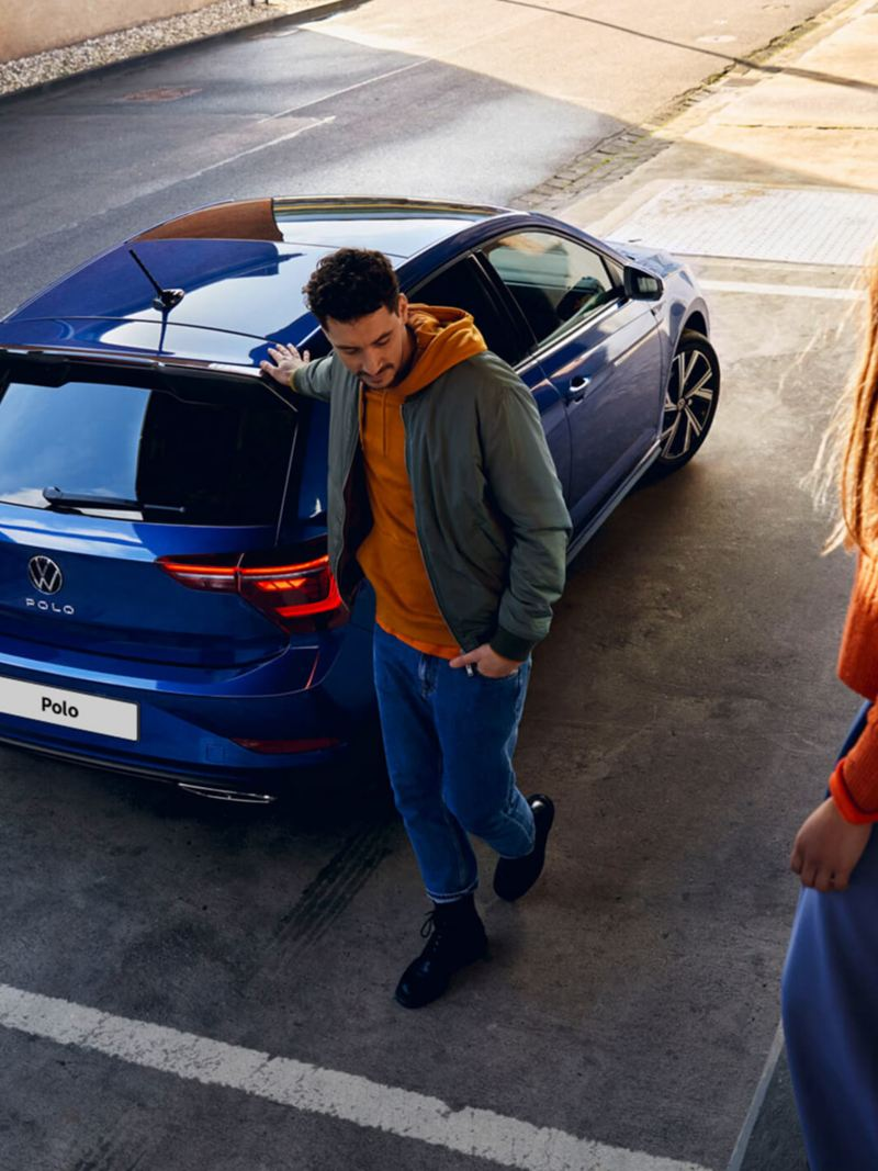A new blue Polo with tinted rear windows is parked in front of a ramp, a woman is sitting on the ramp, a man is walking towards it.