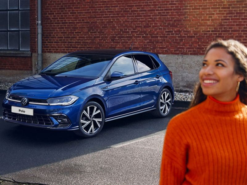 A woman standing next to a blue Polo with the front view of the car