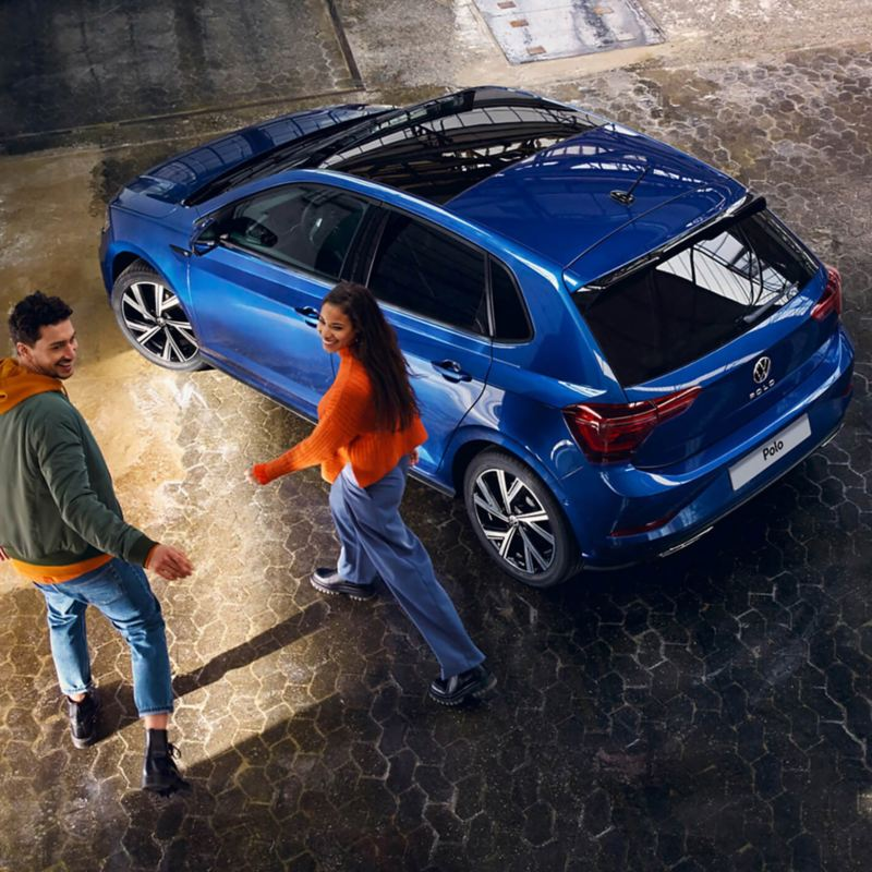A blue VW Polo with a panoramic sliding roof is parked in a hall, a couple is walking towards it.