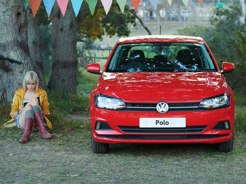 A woman sitting against a tree, by a parked red Polo