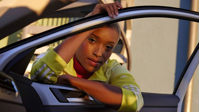 White VW Polo ACTIVE. View of a woman from the inside through an open door and window.