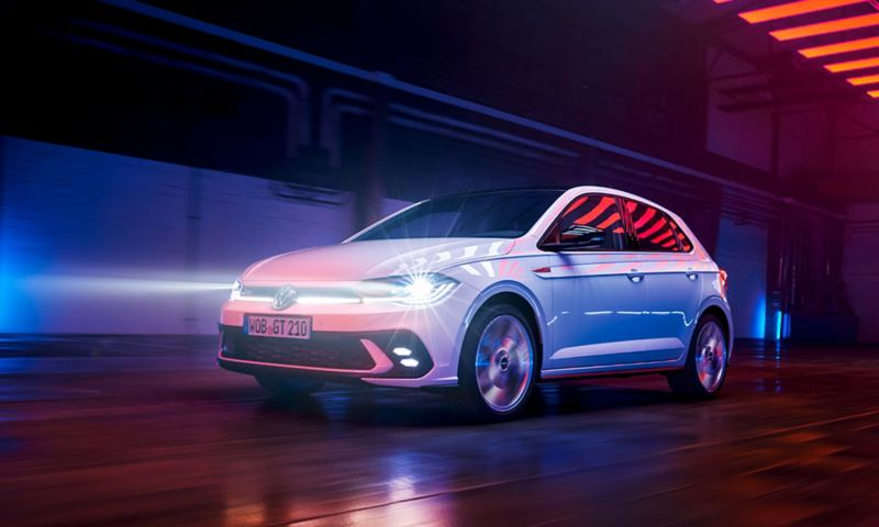 A white VW Polo GTI is driving in a hall with the LED matrix headlights and light bar in the front switched on.