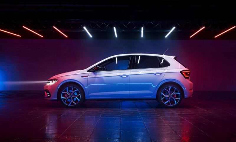 """View of the side of a white VW Polo GTI with tinted rear windows, GTI badge on the fender and optional 18-inch """"Faro"""" wheels."""