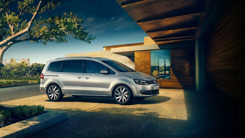 A silver Volkswagen Sharan, parked on the drive of a single story wooden house, trees in the background