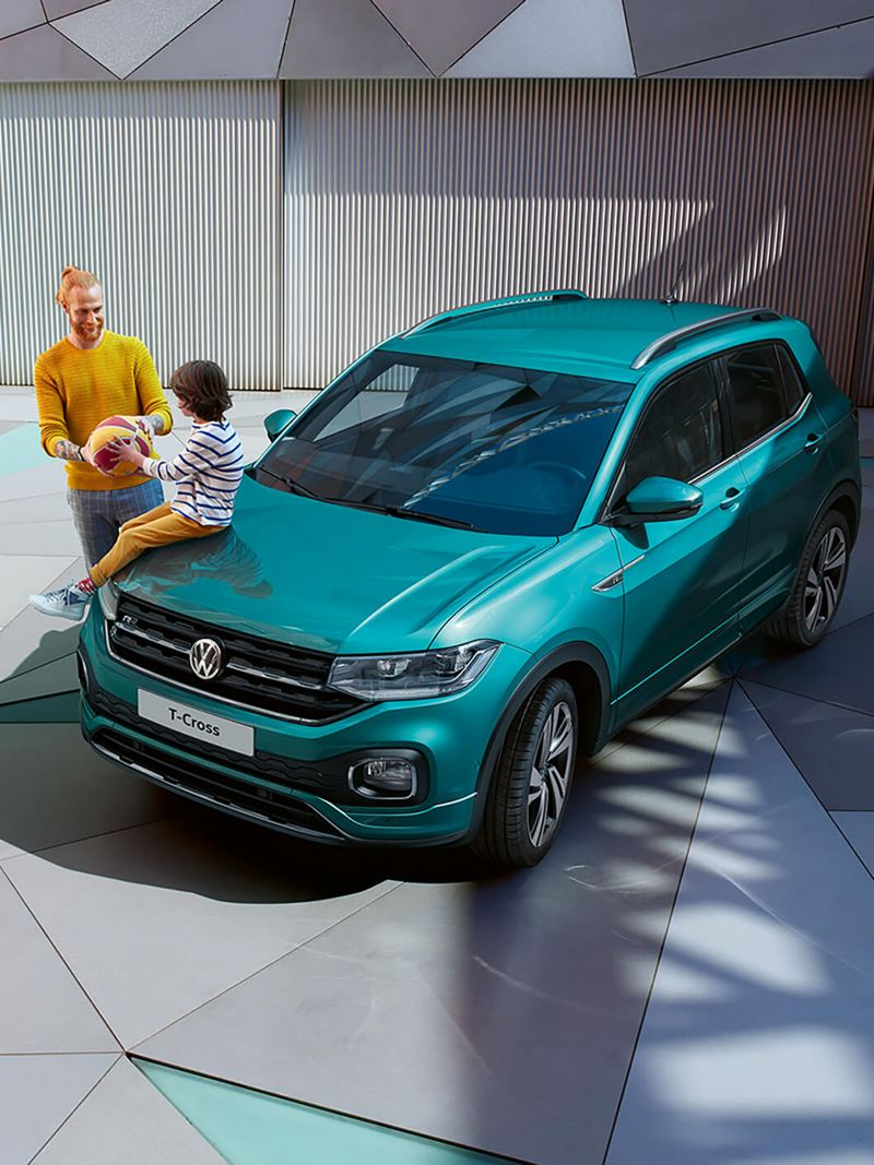 A child sits on the front of a T-Cross with his father holding a ball next to him