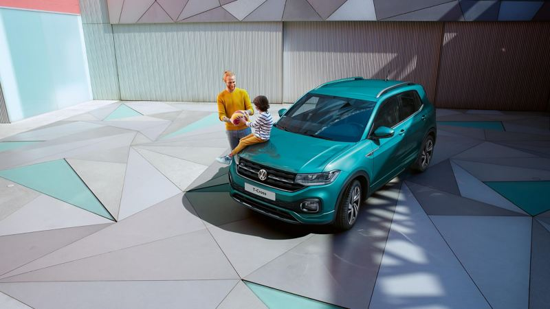 The VW T-Cross parked on a driveway with a father and son playing with a basketball