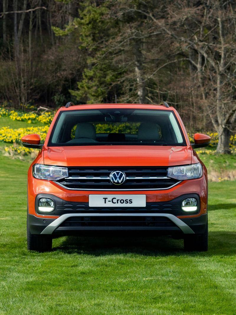 An orange T-Cross parked in a field