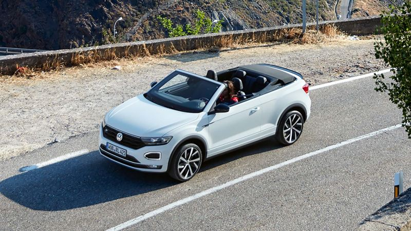 A T-Roc Cabriolet being driven down a mountain road with the roof down