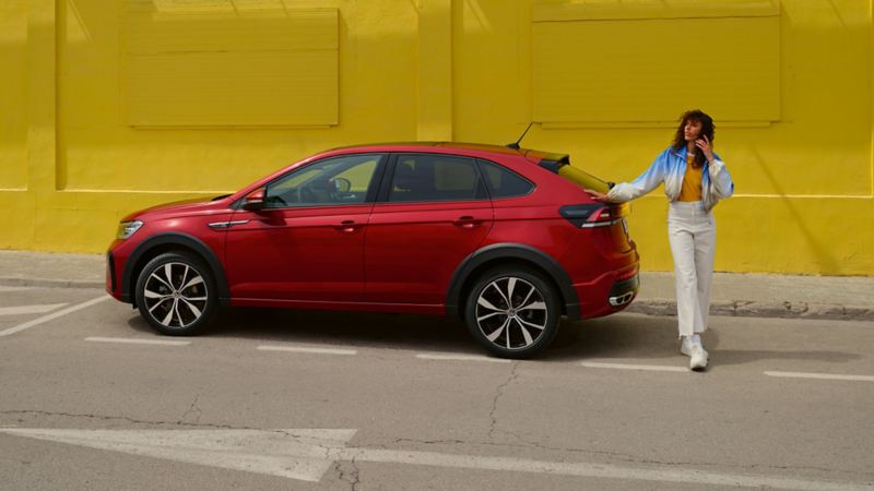 VW Taigo in red on the roadside in front of a yellow building, side view, woman leans on the rear