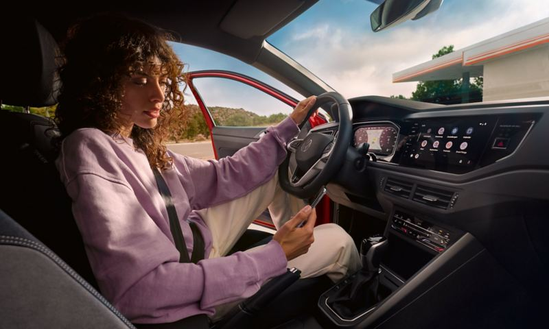 VW Taigo: Woman sits in driver's seat in parked car and looks at smartphone