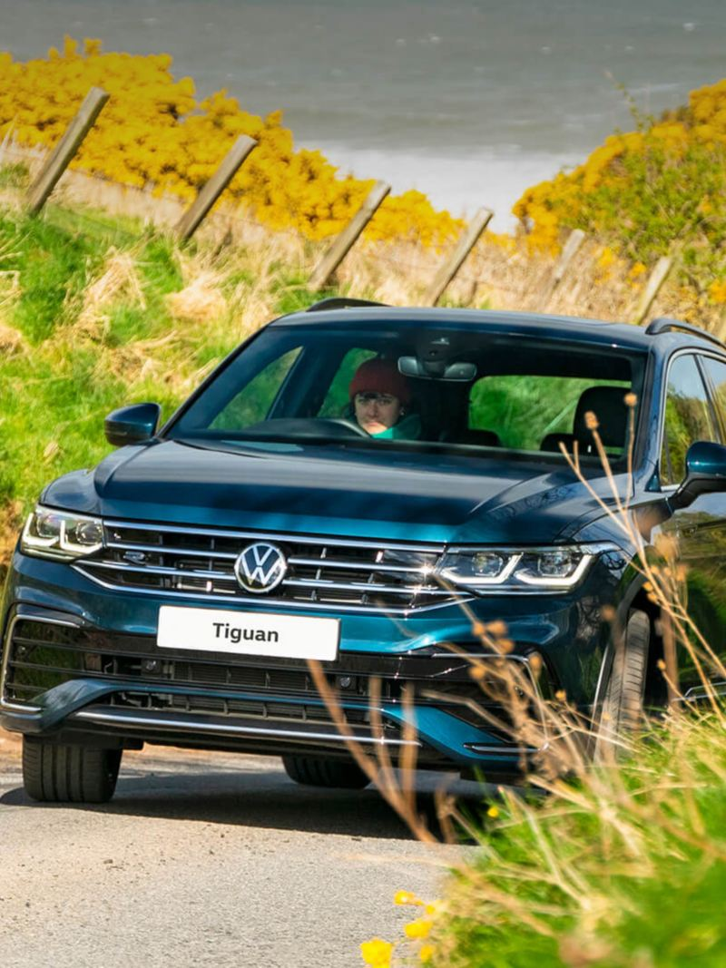 A blue VW Tiguan driving up a windy road in sunny countryside