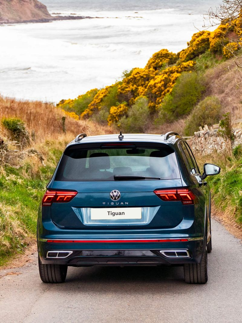 A rear shot of a blue VW Tiguan driving away into the countryside