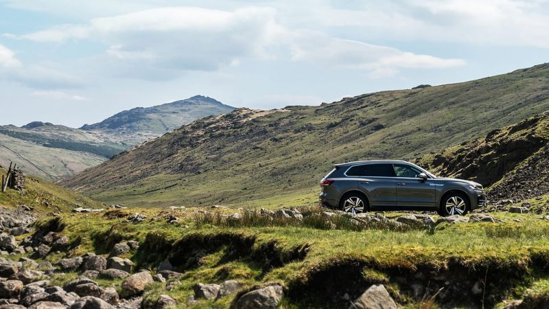 A grey Volkswagen Touareg parked in the mountains.