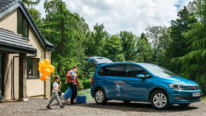 A VW Touran parked in front of a house with a family loading the boot for a day out