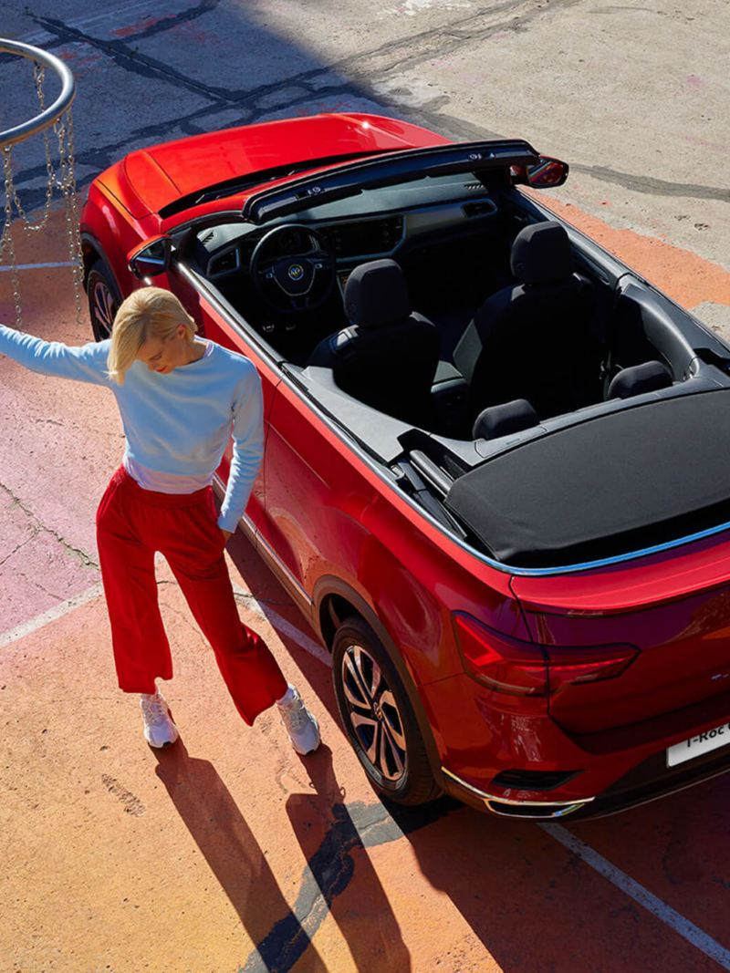 View from above of the red VW T-Roc Cabriolet with an open soft top. A woman is next to it and a basketball basket is visible in the top left corner.
